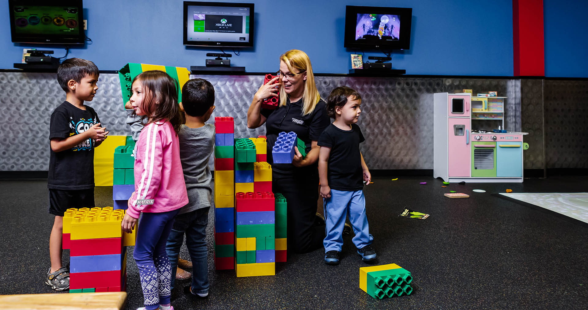 kids with teacher playing with oversized legos
