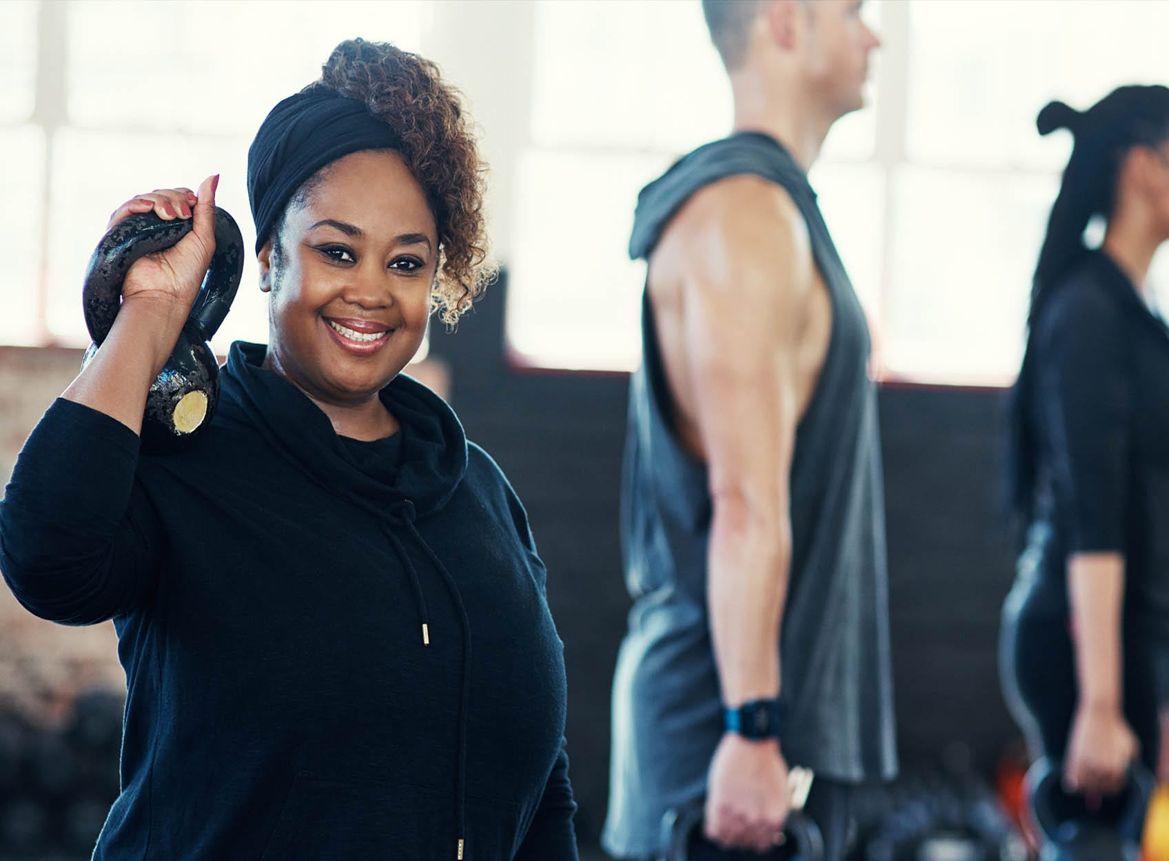 woman holding a kettlebell at a group fitness class