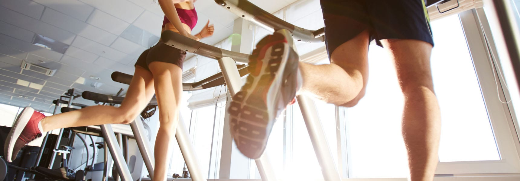 man and a woman running on treadmills