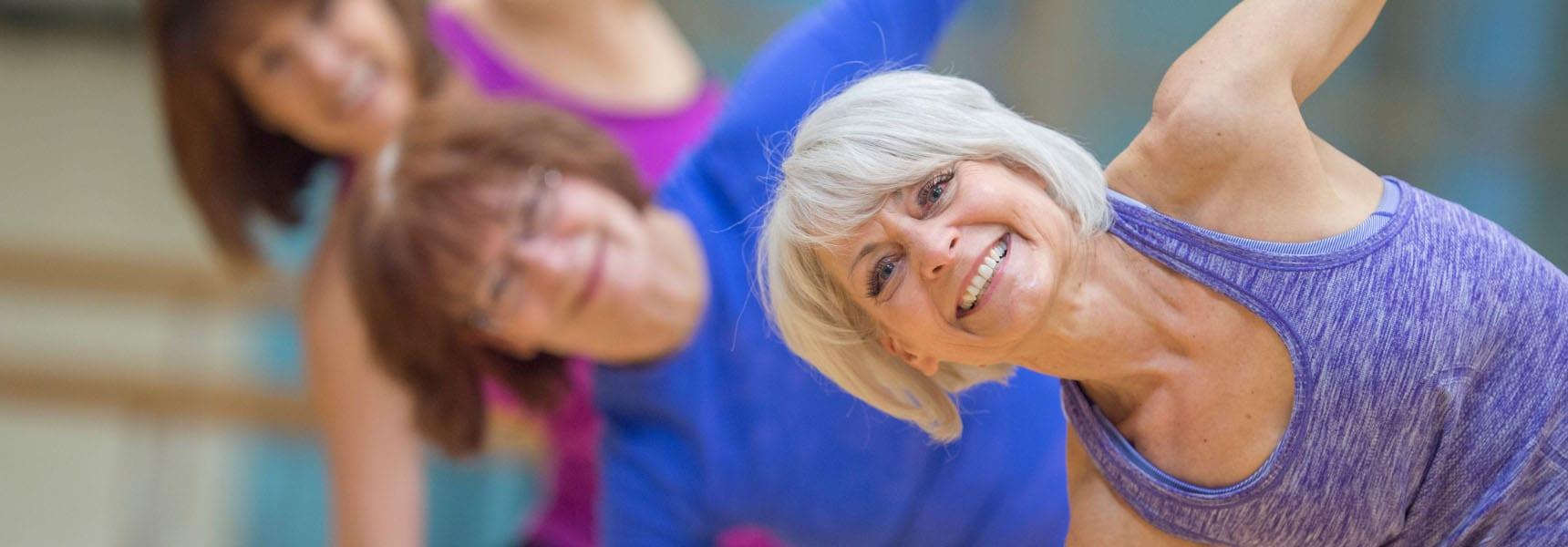 older woman in a yoga class in a modern gym