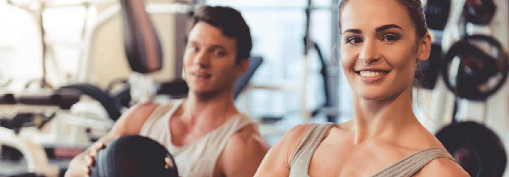 man and woman working out in a modern gym